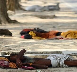 La gente descansa en la calles al refugio de las sombras para protegerse del calor.