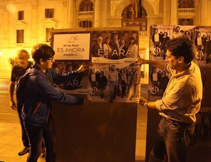 Pilar Lima y Jordi Peris ayuda a una compañera de Podemos a pegar sus cartel.