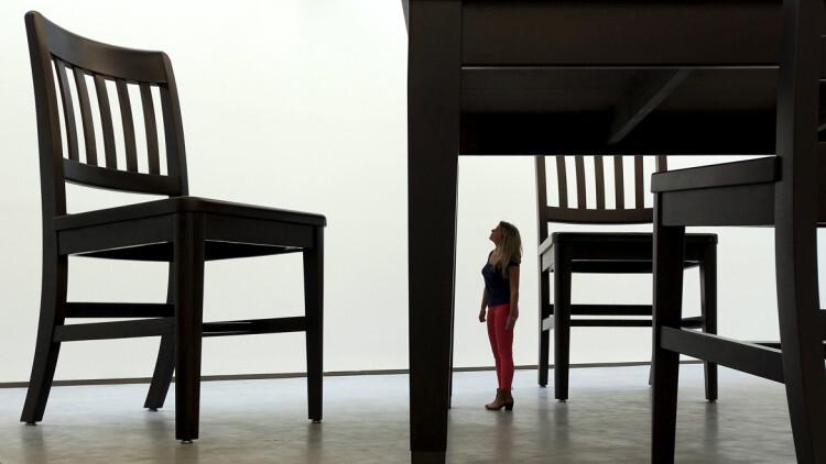 Una mujer contempla la gigantesca escultura de una silla, realizada por el artista Robert Therrien en el Centro de Arte Metropolitano de Belfast, Irlanda del Norte
