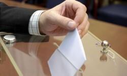Una persona deposita un voto en la urna.
