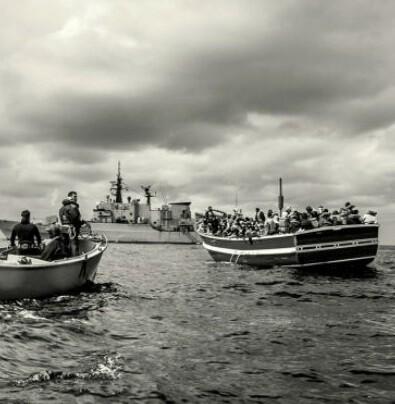 Guardas de salvamento italiano abordan una barca de inmigrantes africanos.