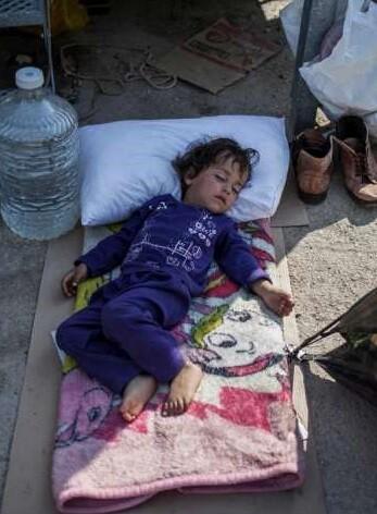 Un niño duerme delante de un centro de registro e identificación en Moria, en la isla de Lesbos.