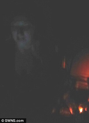 Spooky: This scary snap appears to show a female ghost in old clothing emerging from the floor and casting her eyes down towards a light