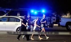 La policía ayuda a salir a los espectadores de la sala. (Foto-AP)