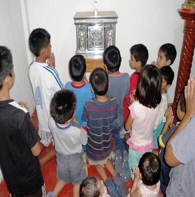Niños y niñas durante un rezo en el Hogar de Nazaret que dirige el pater Ignacio.