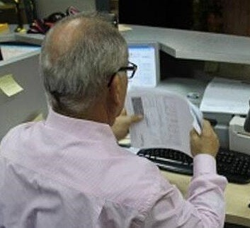 Un funcionario arreglando papeles en una oficina de la administración.