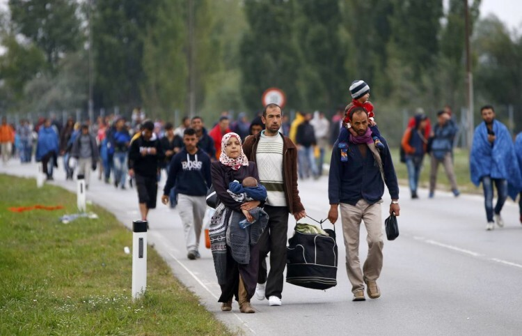 Migrants walk as they cross the border from Hungary to Austria in Nickelsdorf, September 11, 2015. REUTERS/Leonhard Foeger