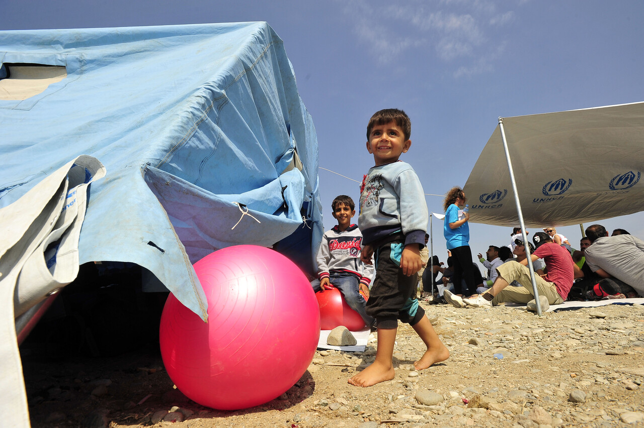 On 26 August, (foreground) Mascut, 3, who is from the Syrian Arab Republic, walks barefoot while playing with a ball, behind a UNICEF-supported child-friendly space, in a reception centre near the town of Gevgelija, on the border with Greece. Another boy sits behind him, while farther back, men rest beneath a shelter whose tarpaulin bears the logo of the Office of the United Nations High Commissioner for Refugees (UNHCR). Mascut, his mother and sister waited six hours in the sun to cross the border into the former Yugoslav Republic of Macedonia. The child-friendly space was established by UNICEF, together with a mobile teams of volunteers from the UNICEF-supported NGO La Strada. The volunteers help reunite children who have become separated from their families, lead recreational activities for children and distribute food and bottled water. In late August 2015 in the former Yugoslav Republic of Macedonia, more than 52,000 people have been registered at the border by police in the town of Gevgelija, after entering from Greece, since June 2015. Since July 2015, the rate of refugees and migrants transiting through the country has increased to approximately 2,000 to 3000 people per day. Women and children now account for nearly one third of arrivals. An estimated 12 per cent of the women are pregnant. Many are escaping conflict and insecurity in their home countries of Afghanistan, Iraq, Pakistan and the Syrian Arab Republic. There are children of all ages traveling with their families. Some are unaccompanied minors aged 16–18 years who are traveling in groups with friends. They are arriving in the country from Greece, transiting to Serbia and further to Hungary, from where they generally aim to reach other countries in the European Union.