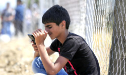 On 26 August, kneeling against a chain-link fence, an adolescent boy uses his hand to shield the screen of his mobile phone from sunlight, in a reception centre near the town of Gevgelija, on the border with Greece. Many refugees and migrants use the mobile messaging application WhatsApp or text messaging to speak with relatives they are meeting at their final destination – or to keep in touch with family members who remain in their country of origin.  In late August 2015 in the former Yugoslav Republic of Macedonia, more than 52,000 people have been registered at the border by police in the town of Gevgelija, after entering from Greece, since June 2015. Since July 2015, the rate of refugees and migrants transiting through the country has increased to approximately 2,000 to 3000 people per day. Women and children now account for nearly one third of arrivals. An estimated 12 per cent of the women are pregnant. Many are escaping conflict and insecurity in their home countries of Afghanistan, Iraq, Pakistan and the Syrian Arab Republic. There are children of all ages traveling with their families. Some are unaccompanied minors aged 16–18 years who are traveling in groups with friends. They are arriving in the country from Greece, transiting to Serbia and further to Hungary, from where they generally aim to reach other countries in the European Union.