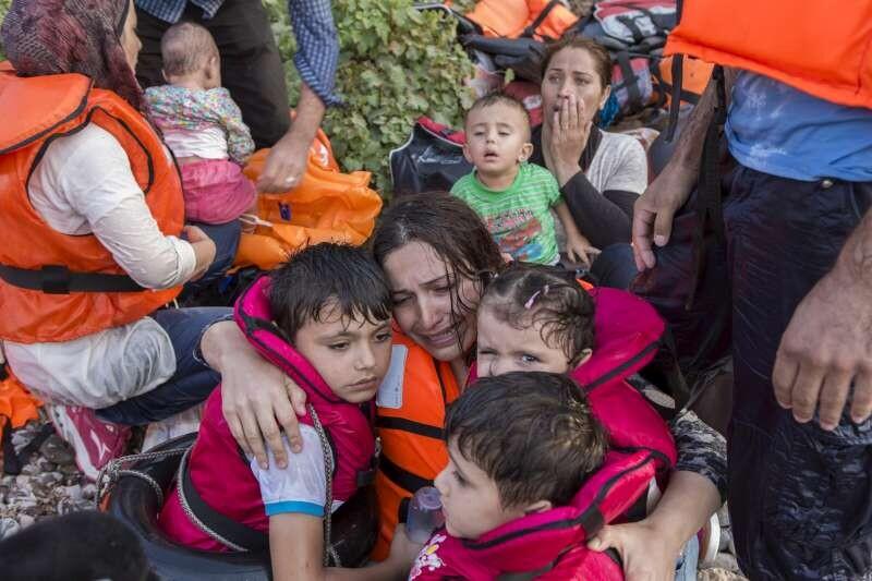 © ACNUR/ I.Prickett.- Una mujer siria llora aliviada mientras abraza a sus tres hijos después de una dura travesía en el Egeo, desde Turquía a la isla griega de Lesbos