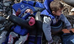 Refugees and migrants arrive at Lesbos island after crossing the Aegean sea from Turkey on October on October 29, 2015. At least seven children died when boats carrying migrants sank off Greece on October 18, as rescue workers battled to save more youngsters on the seashore in the latest desperate scenes in Europe's refugee crisis. Since the start of the year, 560,000 migrants and refugees have arrived in Greece by sea, out of over 700,000 who have reached Europe via the Mediterranean, according to the International Organization for Migration (IOM). AFP PHOTO / ARIS MESSINIS