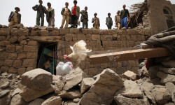 On 4 April, a group of boys and a man standing atop a building destroyed in an air strike watch a rooster land on rubble from the building, in Okash Village, near Sana'a, the capital.  In April 2015 in Yemen, localized conflict between government forces, militants, tribal fighters and other parties since mid-March has spread to many parts of the country. Armed conflict has continued to intensify, and airstrikes, which began on 26 March, have affected 18 of the country's 22 governorates. The escalating violence has taken a significant toll on civilians. By 12 April, an estimated 364 civilians had been killed and 681 had been injured. At least 77 children had also been killed and 44 had been injured. Infrastructure has also been destroyed, damaged or disrupted as a result of the fighting, including airports and bridges, power and water, sanitation and hygiene (WASH) supply, as well as hospitals, educational and religious institutions, factories, farmlands and local markets. Homes are being directly affected by airstrikes and armed clashes, particularly in the south. The intense fighting has caused large-scale displacement, forcing about 150,000 people to flee their homes. Many of the displaced are believed to be staying primarily with relatives or acquaintances, and others are sheltering in schools. However, many of the most-vulnerable are unable to flee to safety. Insecurity, the closure of ports and other restrictions have significantly exacerbated humanitarian needs and hampered access and the delivery of vital aid to vulnerable communities. Food insecurity is rising, with food prices estimated at 40 per cent – and even higher in some areas. The number of people who are food insecure is now estimated at 12 million– a 13 per cent increase since the start of the crisis. Fuel, urgently needed to pump water and to maintain services at hospitals and other critical facilities facing frequent power outages, has run out in many areas and, where available, prices