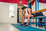 Athletic woman relaxing in a gym locker room after an intensive workout - Tired sportive girl in a fitness center