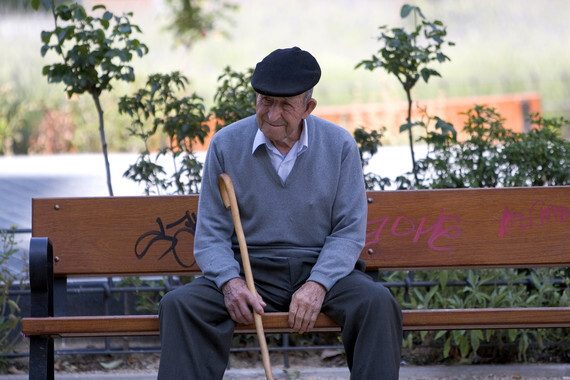 Un se–or mayor sentado en un banco del barrio de Palos de Morguer en Madrid.