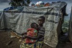 © UNHCR/ACNUR/F. Noy - Un niña congolesa desplazada interna pela verduras mientras cuida de su hermana en Kivu Nortu, RDC.