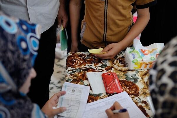 Desplazados rellenando formularios de asistencia humanitaria en Kirkuk, Iraq. (Foto- UNICEF-Lindsay Mackenzie).