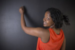South African or African American woman teacher or student writing on chalk black board background