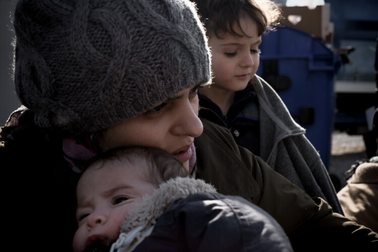 "On 28 November, Nour Majati cradles her 1-month-old son, Youssef, in the village of Tabanovce, on the border with Serbia. Her 5-year-old son, Basher, is behind them. Mrs. Majati, her husband and their four children are making their way to the Serbian border after arriving in the village by train. They fled the Syrian city of Halab (Aleppo) following bombing attacks on their home by government allies after Mr. Majati joined the opposition during the escalating conflict. The family initially found refuge in a nearby town but were forced to leave the country altogether after that town was overrun by ISIS. Mrs. Majati, who was pregnant with Youssef at the time, gave birth via Caesarean section operation just before they fled. Her surgical wound opened during the long, arduous journey: overland in Turkey, by sea to Greece, and overland again – walking for days – towards Central Europe. She was forced to let the wound heal on its own, and although it eventually stopped bleeding, it remains very painful. Her body is also swollen, and it takes her twice as long to walk anywhere. She is often also sick as a result of the cold weather, which she believes is making Youssef, whom she breastfeeds, ill as well. Mrs. Majati hopes to find ""safety, rest, treatment, and education – most importantly, education"" in Sweden, the family's final destination. ""I have been looking for humanity, but much of the time, I cannot find it. I realized that the Syrian blood is very cheap,"" she said. ""The help that we received throughout the journey showed me that there is still a little hope,"" she added. The family visited a UNICEF child-friendly space in the village, where they dressed their children in warm clothes provided by an aid group and also received soup, before continuing their journey north. In late November 2015, refugee and migrant flows into Europe remain at an unprecedented high. Since the beginning of the year, over 870,000 refugees and migrants have crossed t"