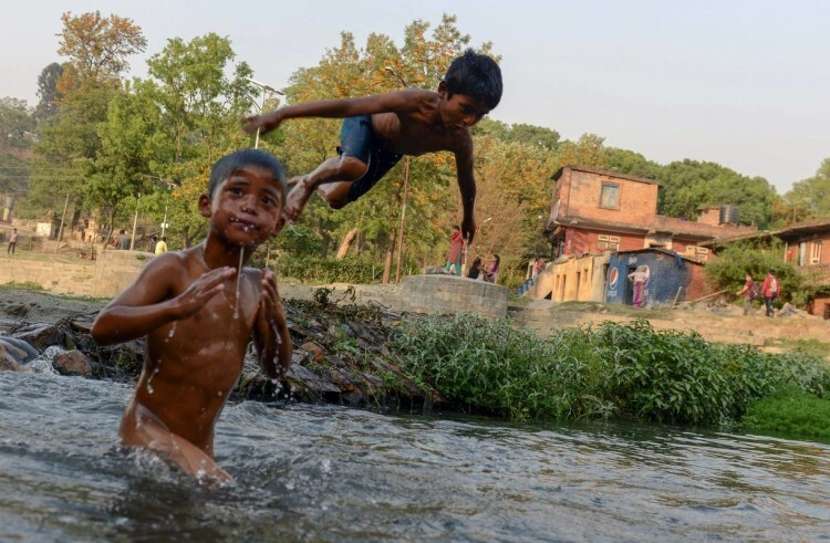 Nepalese boys swim in a river as they beat the summer heat in Kathmandu on April 22, 2016. / AFP PHOTO / PRAKASH MATHEMA