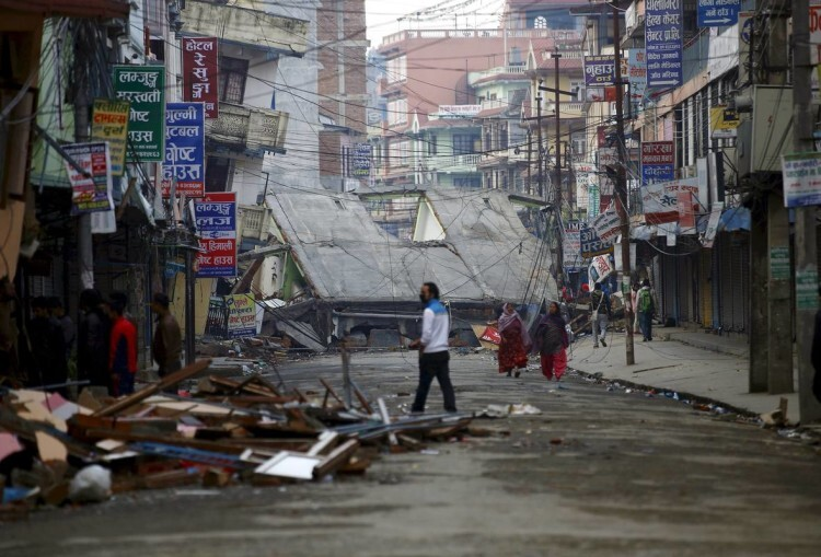 People walk along a deserted road near a collapsed house after an earthquake in Kathmandu, Nepal April 29, 2015. REUTERS/Navesh Chitrakar /File Photo