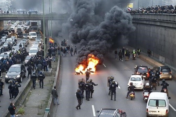 Anti-riots policemen arrive as taxi drivers block the traffic during a demonstration against the VTC  transport vehicle with chauffeur  on January 26  2016 on the ringroad  peripherique   at porte Maillot in Paris  AFP PHOTO   THOMAS SAMSON