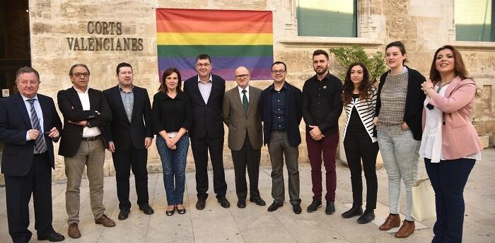 La puerta principal del Palacio de los Borja, sede de les Corts Valencianes, luce hoy la bandera del arco iris, señera del movimiento LGTB.