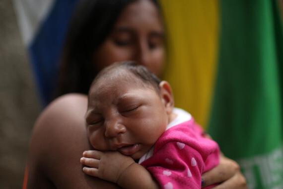 """BRASIL ZIKA:BRA01. RÍO DE JANEIRO (BRASIL), 11/02/2016.- Fotografía del 11 de febrero de 2016, en Río de Janeiro (Brasil) de la madre Leticia de Araujo Aguiar (i), mientas sostiene su hija, Manuelly Araujo da Cruz, de un mes de nacida, quien hace parte de la lista de niños que nacieron con microcefalia al haberse visto expuesta al virus del zika durante su gestación. Leticia de Araujo, que contrajo zika en su tercer mes de embarazo y dio a luz a Manuelly, asegura que es viable criarla, """"se aprende a ser madre de un niño normal y de un niño con microcefalia"""", comentó a Efe. """"La única diferencia es que Manuelly tiene una hora en la que llora mucho"""" y """"se pone muy nerviosa, agitando los brazos"""", pero """"fuera de eso es normal"""". EFE/ Antonio Lacerda."""