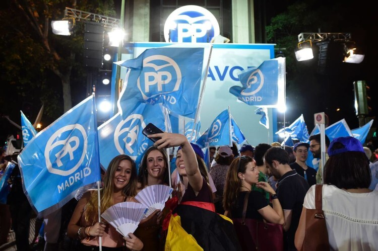Young supporters of the Popular Party (PP) pose for a selfie as they wait outside the PP headquarters during Spain' class=