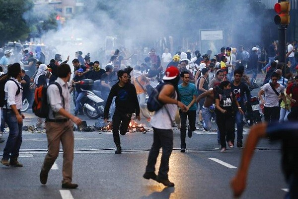 Demonstrators run away from tear gas during a protest in Caracas February 12, 2014.  A demonstrator was killed during an anti-government rally in Caracas on Wednesday, Reuters witnesses said. A Reuters cameraman and a photographer both heard shots and saw one protester had fallen to the ground. The person was then carried away dead. REUTERS/Jorge Silva (VENEZUELA - Tags: POLITICS CIVIL UNREST)