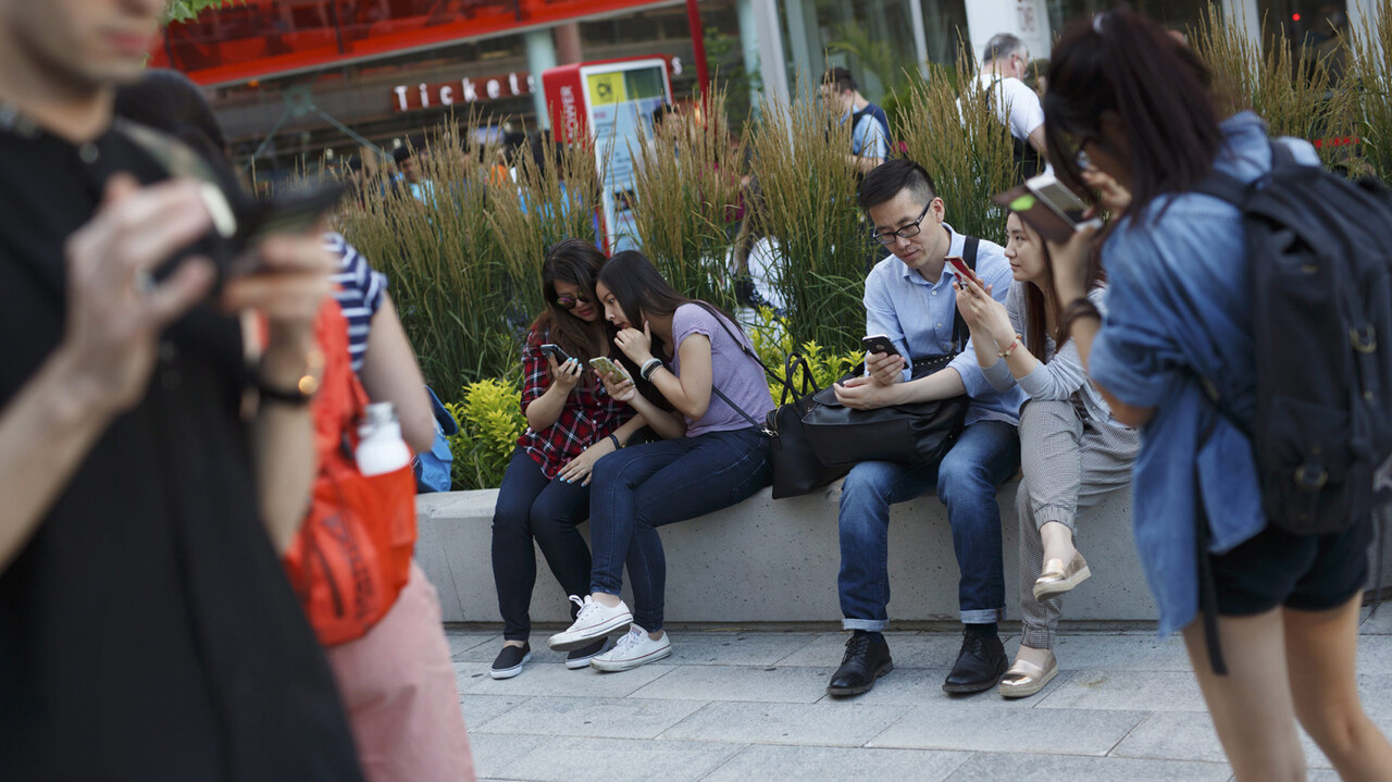 """Gamers use their phones during a """"Pokemon Go"""" smartphone game release party in Toronto, Monday, July 18, 2016. (Cole Burston/The Canadian Press via AP)"""