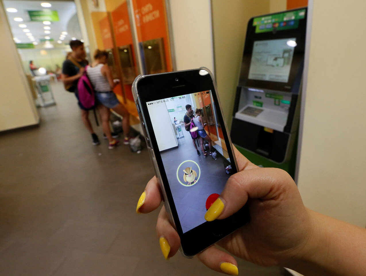 """A woman plays the augmented reality mobile game """"Pokemon Go"""" by Nintendo, as a visitors use an automated teller machine (ATM) at a branch of Sberbank in central Krasnoyarsk, Siberia, Russia, July 20, 2016. REUTERS/Ilya Naymushin"""