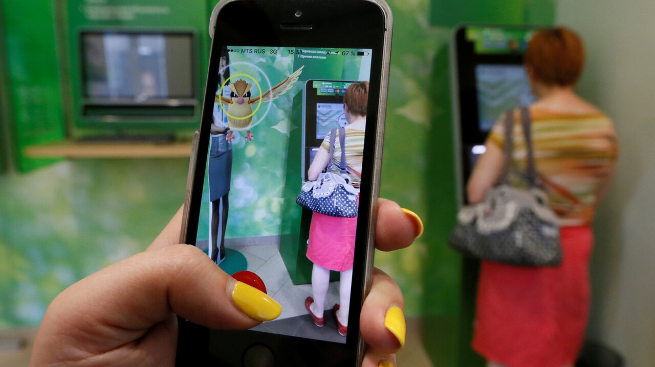 """A woman plays the augmented reality mobile game """"Pokemon Go"""" by Nintendo, as a visitor uses an automated teller machine (ATM) at a branch of Sberbank in central Krasnoyarsk, Siberia, Russia, July 20, 2016. REUTERS/Ilya Naymushin"""