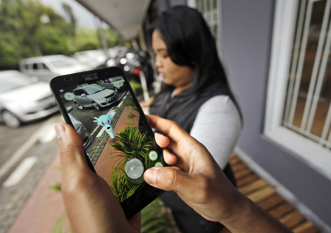 """In this Monday, July 18, 2016 photo, people play """"Pokemon Go"""" in Jakarta, Indonesia. Indonesian authorities banned the playing of """"Pokemon Go"""" from the presidential palace on Wednesday, July 20, 2019, as they voiced worries that the game could be a security risk. (AP Photo/Achmad Ibrahim)"""