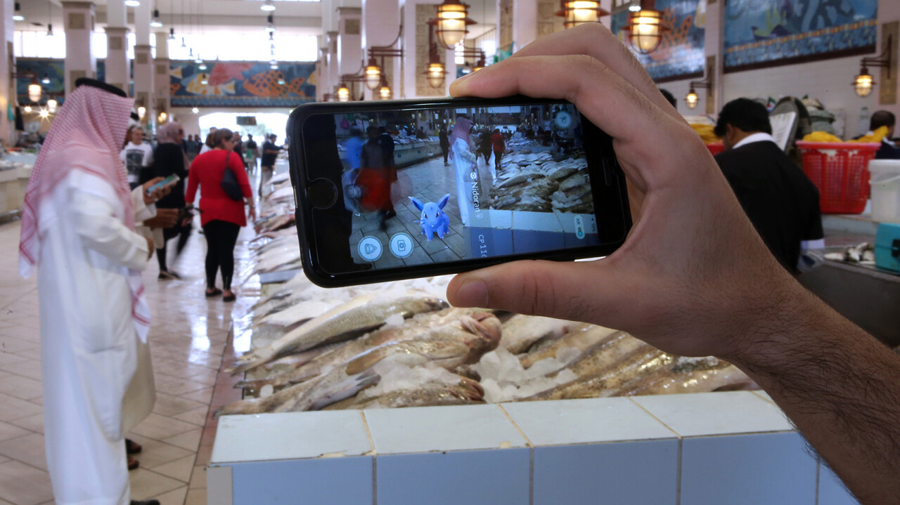 A gamer uses the Pokemon Go application on his mobile in the main fish market in Kuwait City on July 14, 2016. / AFP PHOTO / YASSER AL-ZAYYAT