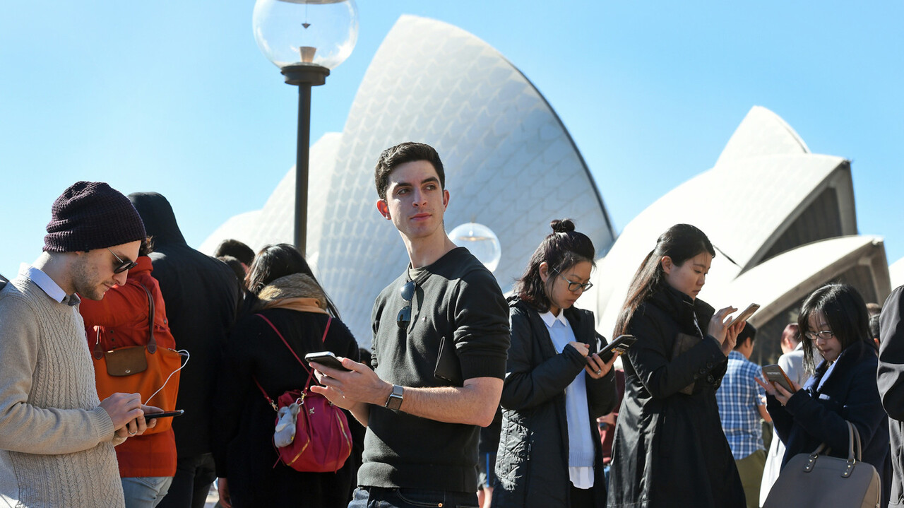 Dozens of people gather to play Pokemon Go in front of the Sydney Opera House on July 15, 2016. The wildly popular mobile app, which is based on a 1990s Nintendo game, has created a global frenzy as players roam the real world looking for cartoon monsters and was launched in Australia last week. / AFP PHOTO / William WEST