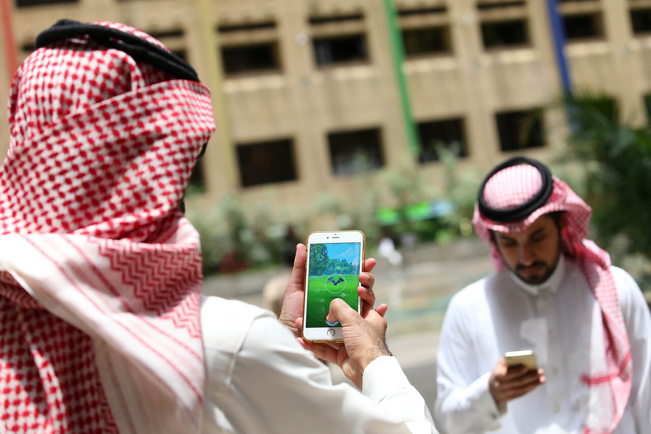Saudi men play with the Pokemon Go application on their mobiles in the capital Riyadh on July 17, 2016. / AFP PHOTO / STRINGER