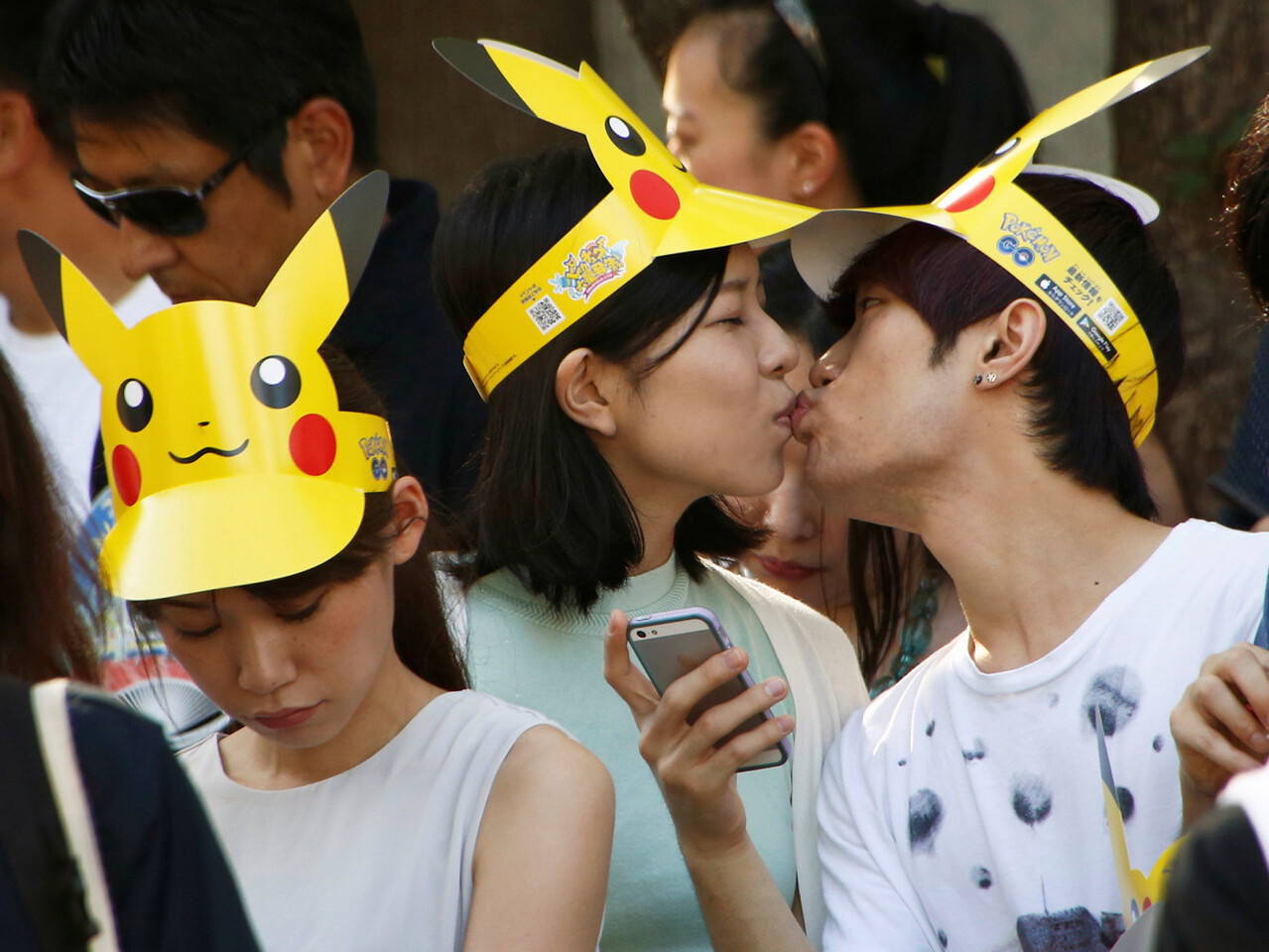 A couple kisses as they wait for start of a parade by Pokemon characters in Yokohama, Japan, August 7, 2016. REUTERS/Kim Kyung-Hoon