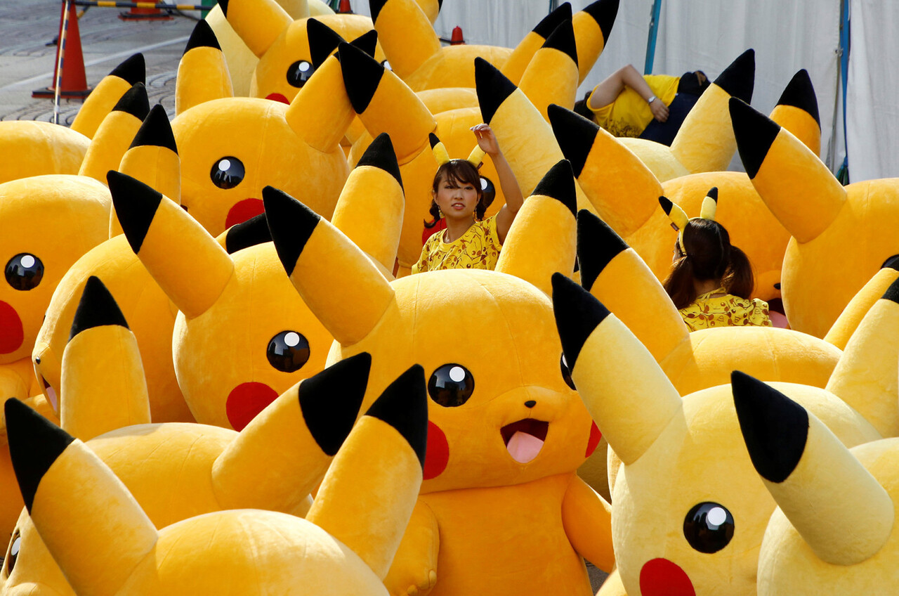 A staff guides performers wearing Pokemon' class=