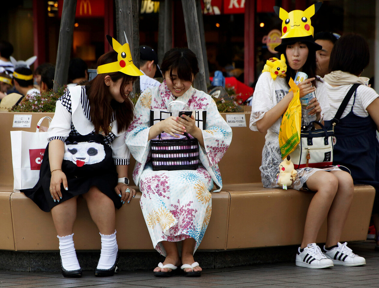 A girl clad in a yukata, or a casual summer kimono, and women wearing hats of Pokemon' class=
