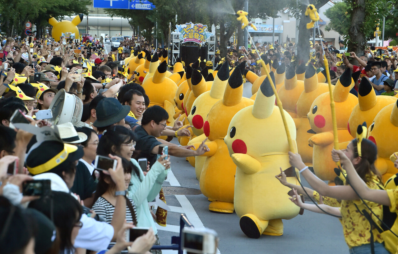 Performers dressed as Pikachu, the popular animation Pokemon series character, perform in the Pikachu parade in Yokohama on August 7, 2016.  Some 50 life-size Pikachu characters, the most famous from the Pokemon game, marched along the city' class=