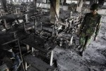 An army personnel inspects the burnt machineries of a garment factory after a devastating fire in Savar November 25, 2012. A fire swept through a garment factory on the outskirts of Bangladesh's capital killing more than 100 people, the fire brigade said on Sunday, in the country's worst ever factory blaze. REUTERS/Andrew Biraj (BANGLADESH - Tags: DISASTER BUSINESS TEXTILE MILITARY)