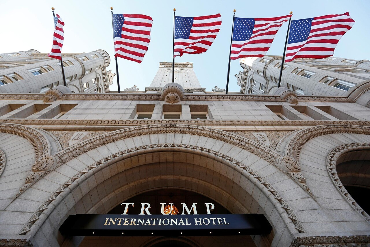 Flags fly above the entrance to the new Trump International Hotel on it' class=