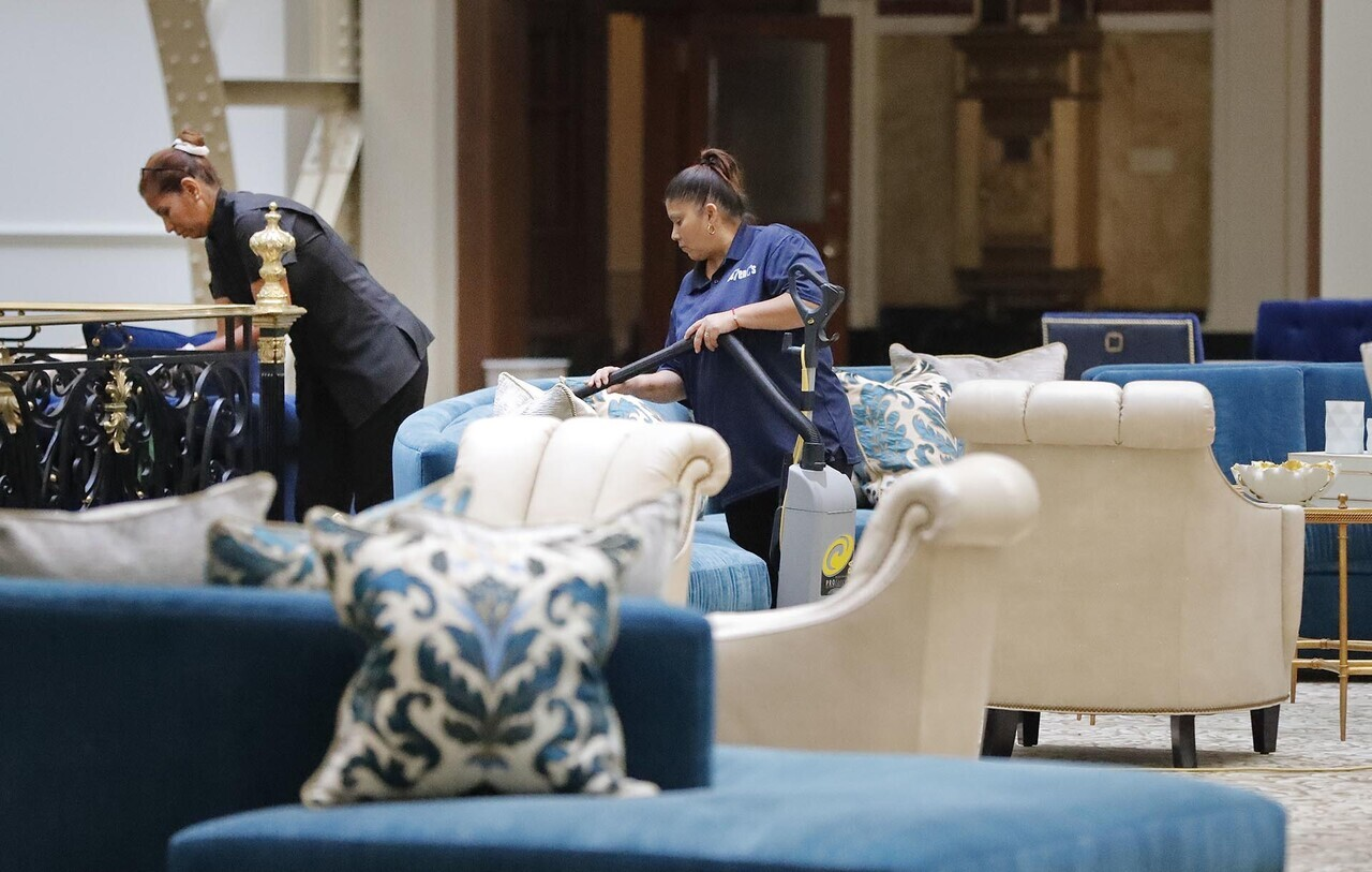 Workers vacuum furniture in the lobby at the Trump International Hotel in downtown Washington, Monday, Sept. 12, 2016 in Washington. The luxury hotel Donald Trump has built in an iconic downtown Washington building is set to open. The Trump International Hotel will begin serving guests Monday. There won' class=