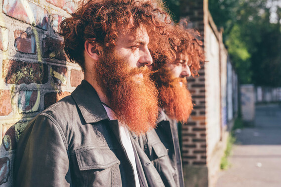 Young male hipster twins with red hair and beards leaning against brick wall