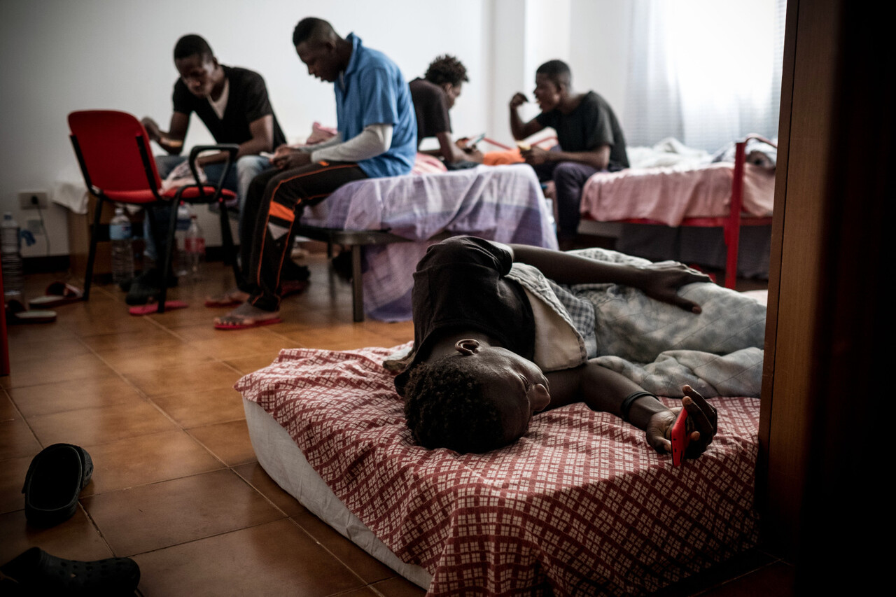 """A boy lies on a bed while others are seen behind, in their room at an unaccompanied minor shelter in Trabia, Italy, on May 19, 2016. The boys live at Rainbow, a government administered center for unaccompanied boys that provides shelter, food, education and legal help for unaccompanied asylum seekers in Trabia, Sicily. Of the 150,000 migrants and refugees who arrived in Italy in 2015, the vast majority of people are coming from West Africa. In May 2016, since the beginning of 2016, almost 184,500 people have crossed the Mediterranean to seek safety and protection in Europe. Following the significant change in the situation in south-eastern Europe, UNICEF is revising its funding needs and programmatic response to adapt to the needs of refugee and migrant children in Greece, Turkey, Italy and other European countries. One of the main challenges in the current situation is reaching """"invisible"""" refugee and migrant children, taking dangerous illegal routes and facing heightened risks of abuse, exploitation and trafficking."""