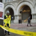"""A construction worker takes down caution tape outside the Trump International Hotel in Washington, DC, September 12, 2016, next to a placard placed by protesters from Answer Coalition calling to """"Dump Trump."""" / AFP PHOTO / JIM WATSON"""