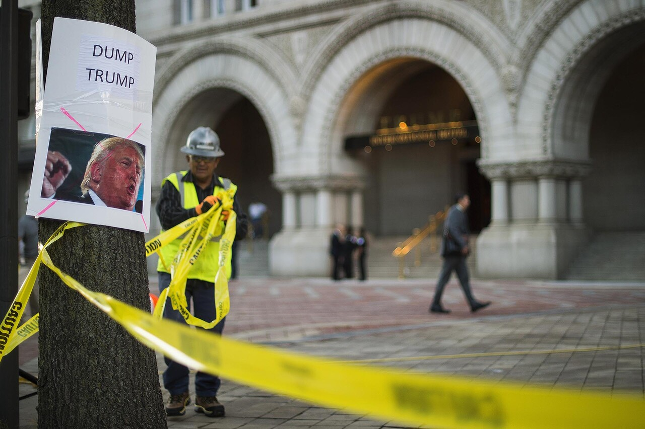 "A construction worker takes down caution tape outside the Trump International Hotel in Washington, DC, September 12, 2016, next to a placard placed by protesters from Answer Coalition calling to ""Dump Trump."" / AFP PHOTO / JIM WATSON"