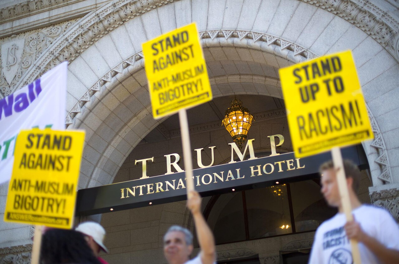 Demonstrators stand outside the Trump International Hotel during it' class=