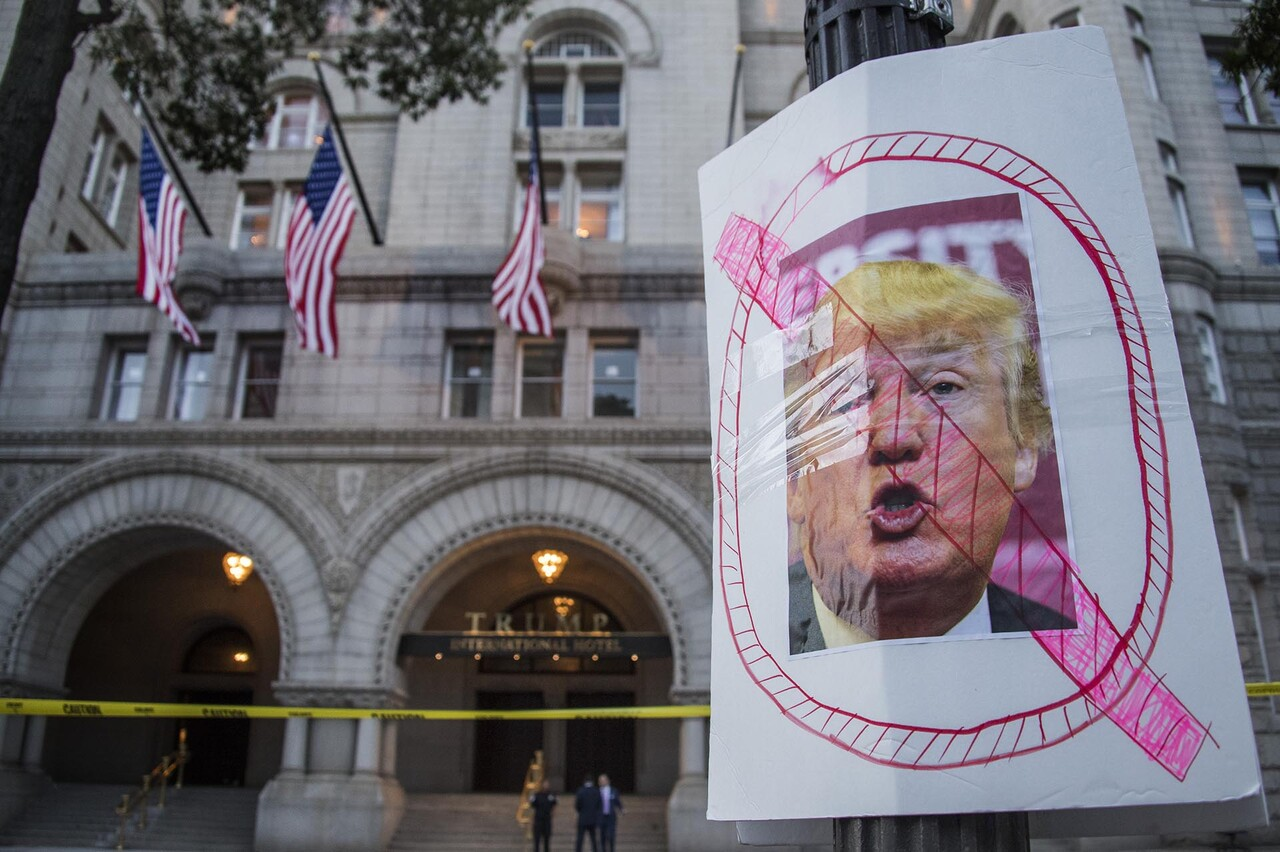 A placard placed by protesters from Answer Coalition stands outside the Trump International Hotel in Washington, DC, September 12, 2016, ahead of the hotel' class=