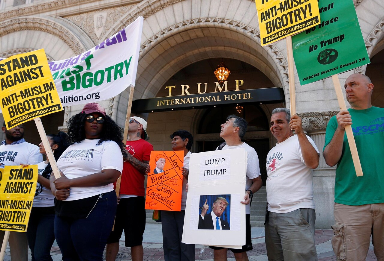 Protesters hold signs outside the new Trump International Hotel on it' class=